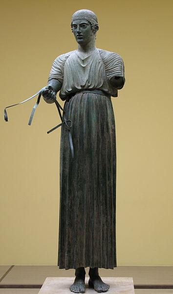 Woźnica z Delf jest ubrany w chiton. posąg pochodzi z V w p.n.e. Źródło
