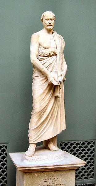 Demostenes, wielki mówca i wódz grecki, przeciwnik Macedończyków: Aleksanda i jego ojca Filipa. Tu jest omotany hlamidą jako jedynym okryciem. Źródło.